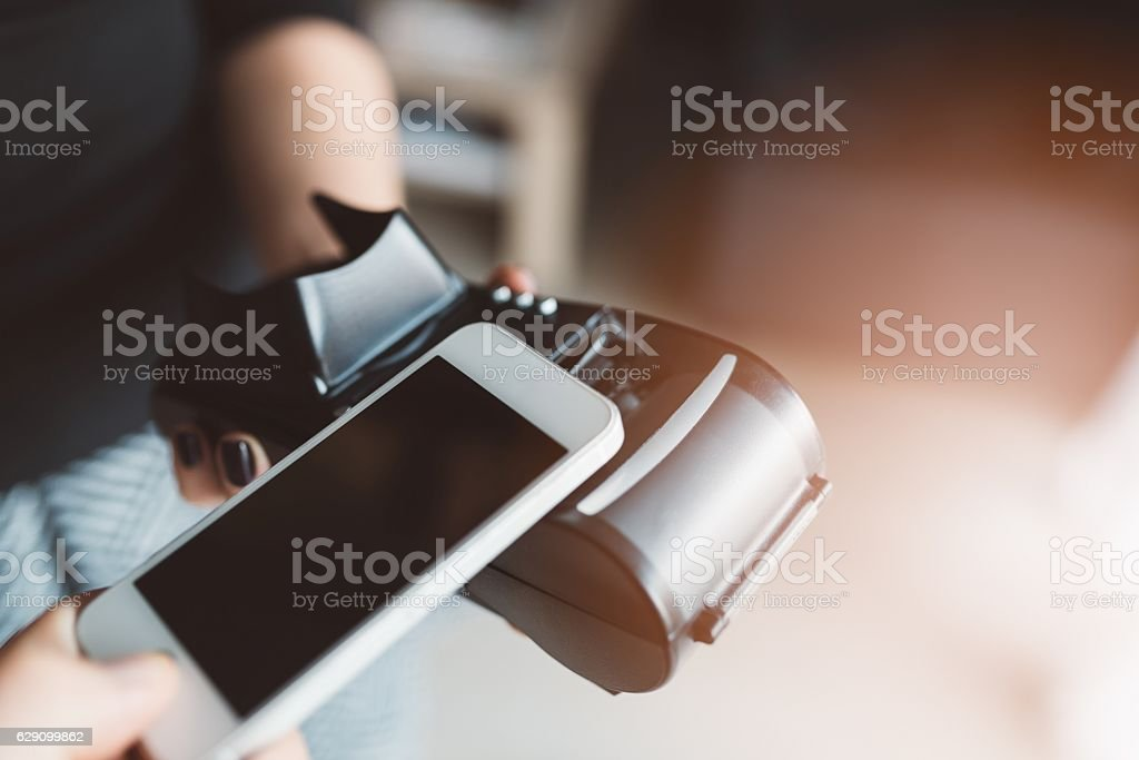 Man using NFC technology on smart phone to pay stock photo