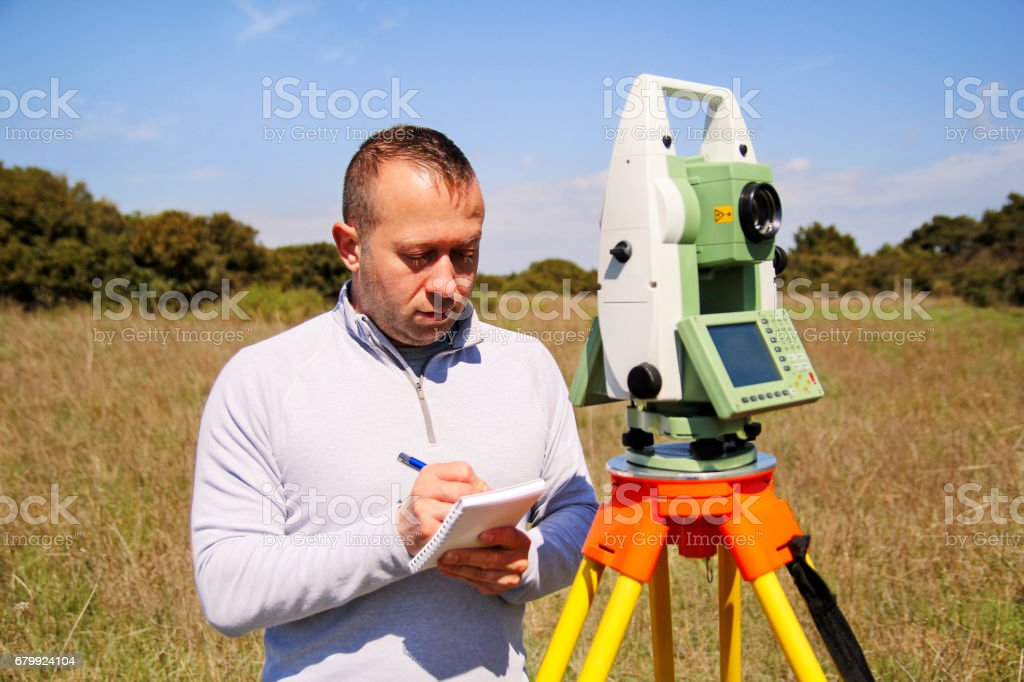Man using of total station. Guy surveyor at work. Survey Instrument geodetic device, total station set and surveyor worker making measurement in the field. Total station outdoor at construction site. stock photo
