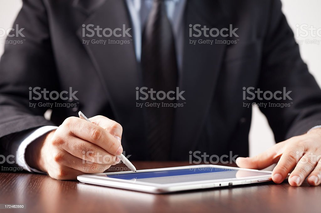 Man using pen to sign digital signature on a digital tablet stock photo