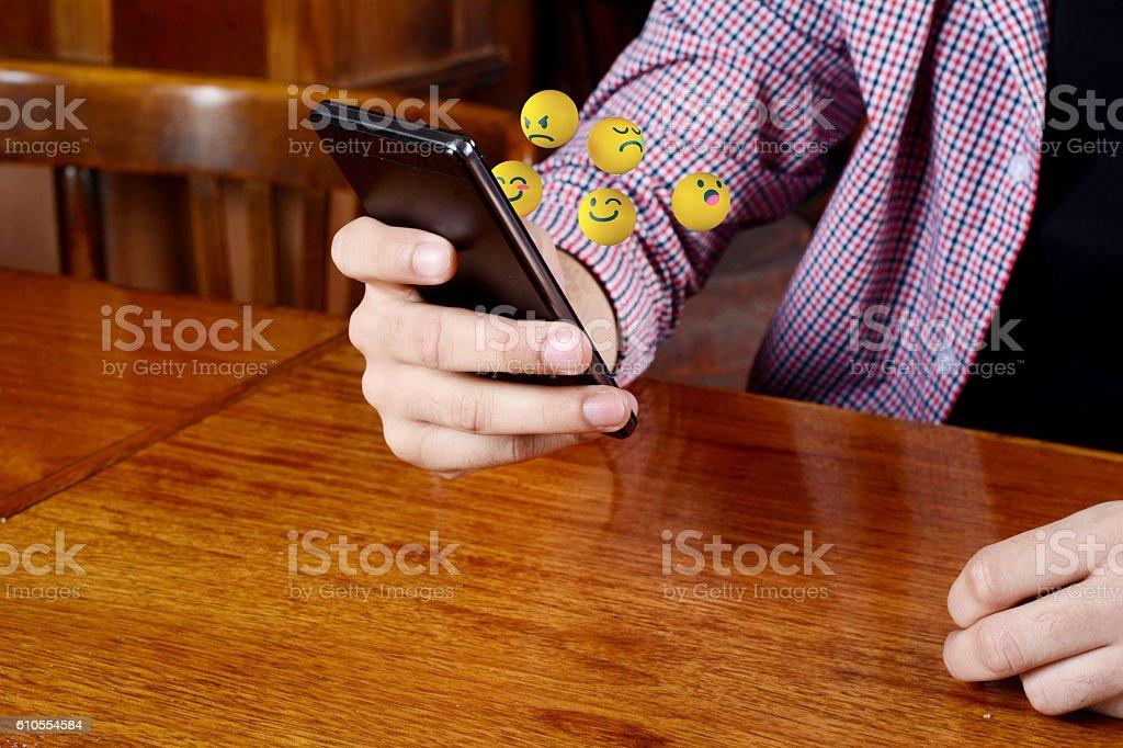 Man using phone sending emojis stock photo