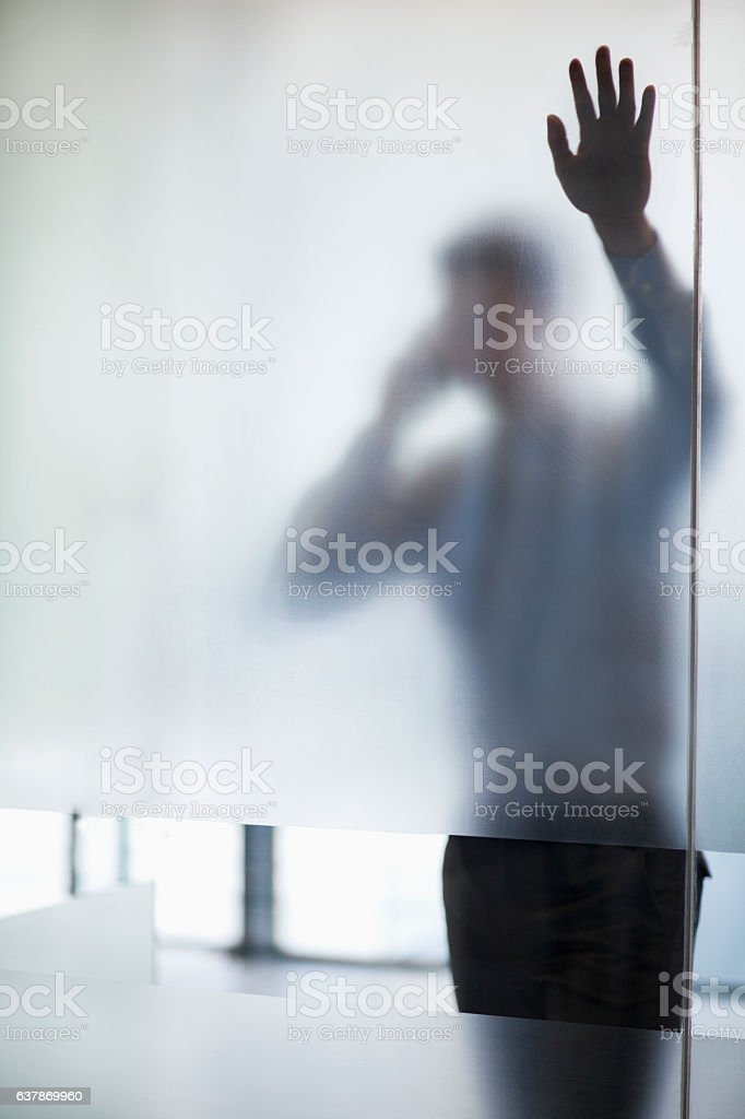 Man using phone with hand on glass wall stock photo