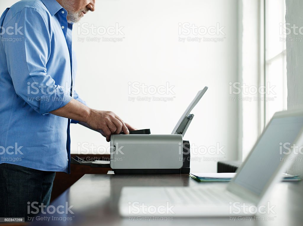 Man Using Printer At Study Table In House stock photo