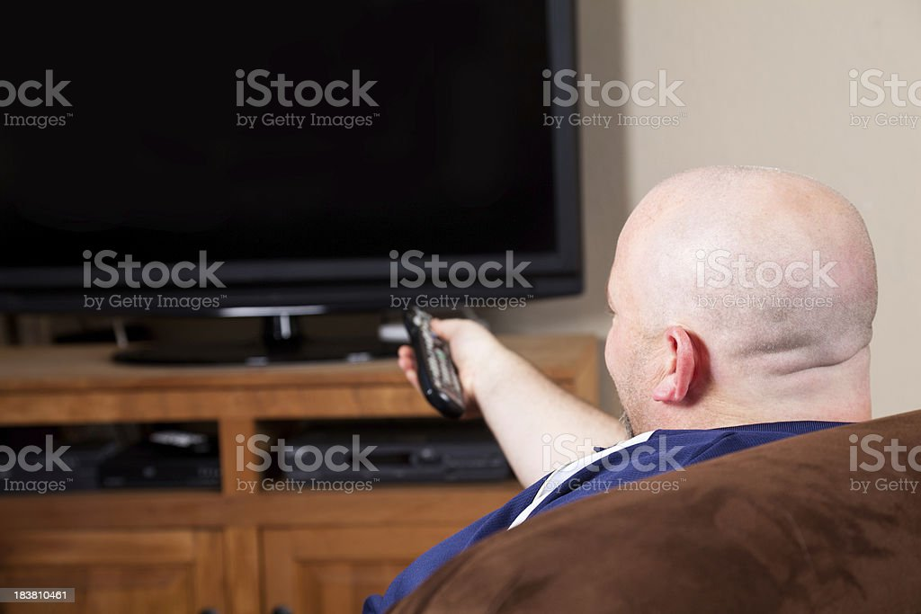 Man Using Remote While Watching TV royalty-free stock photo