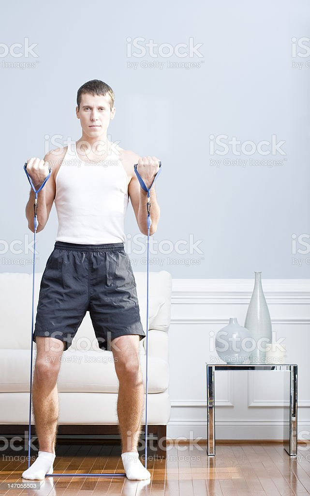 Man Using Resistance Bands in Living Room stock photo