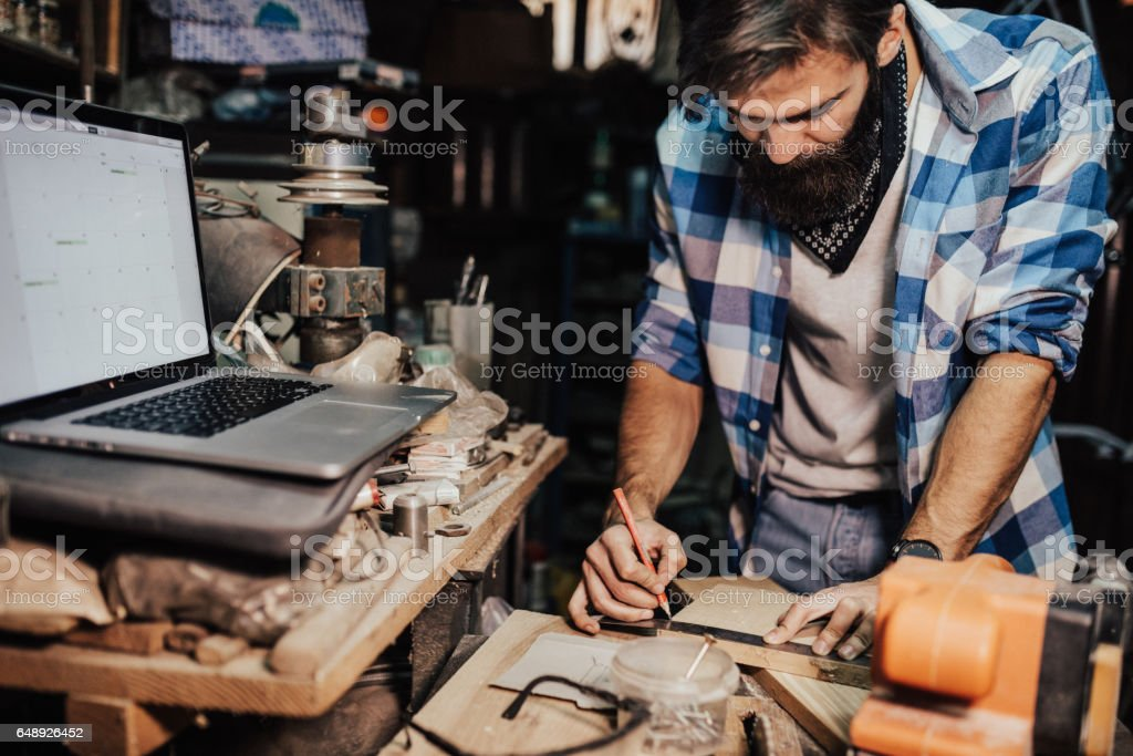 Man using ruler and pencil to mark where to cut stock photo