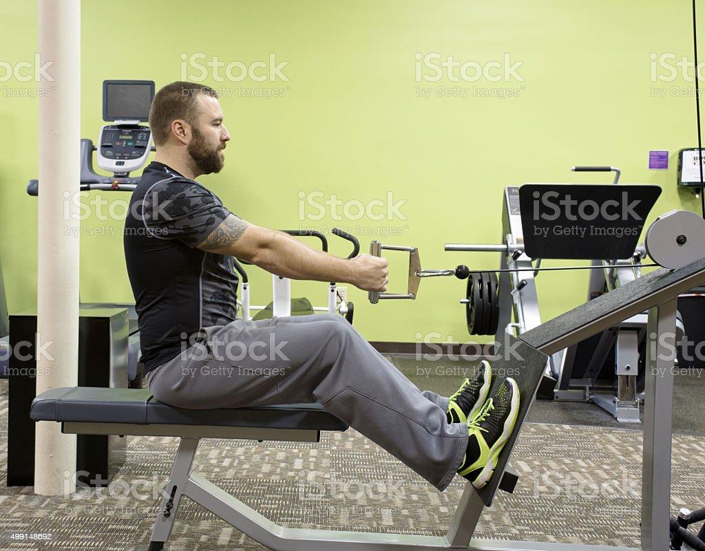 Man Using Seated Row Machine stock photo