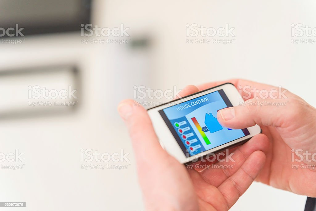 Man using smart phone for remote house control stock photo