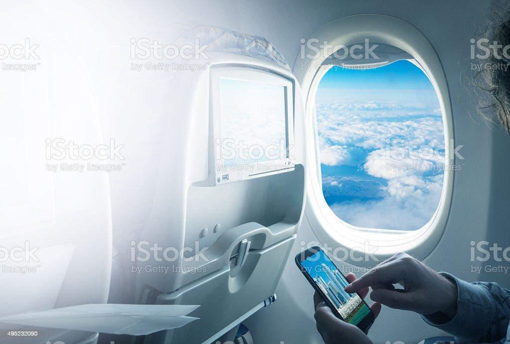 Man using smart phone in  airplane stock photo