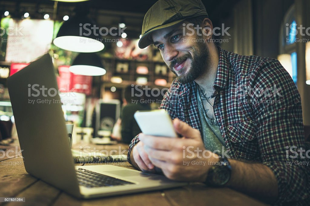 Man using smart phone in cafe stock photo