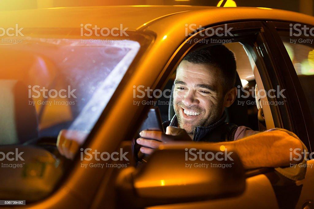 Man using smart phone in car at night stock photo