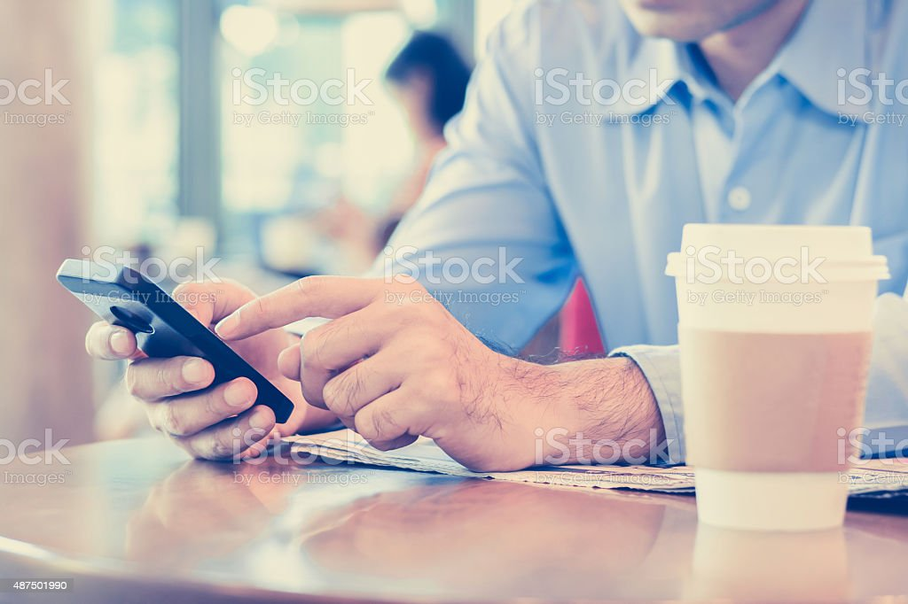 Man using smart phone in coffee shop stock photo