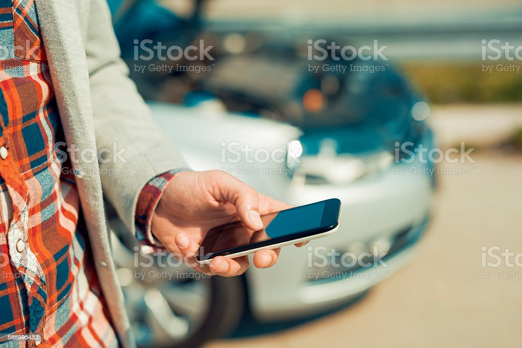 Man using smartphone after traffic accident stock photo