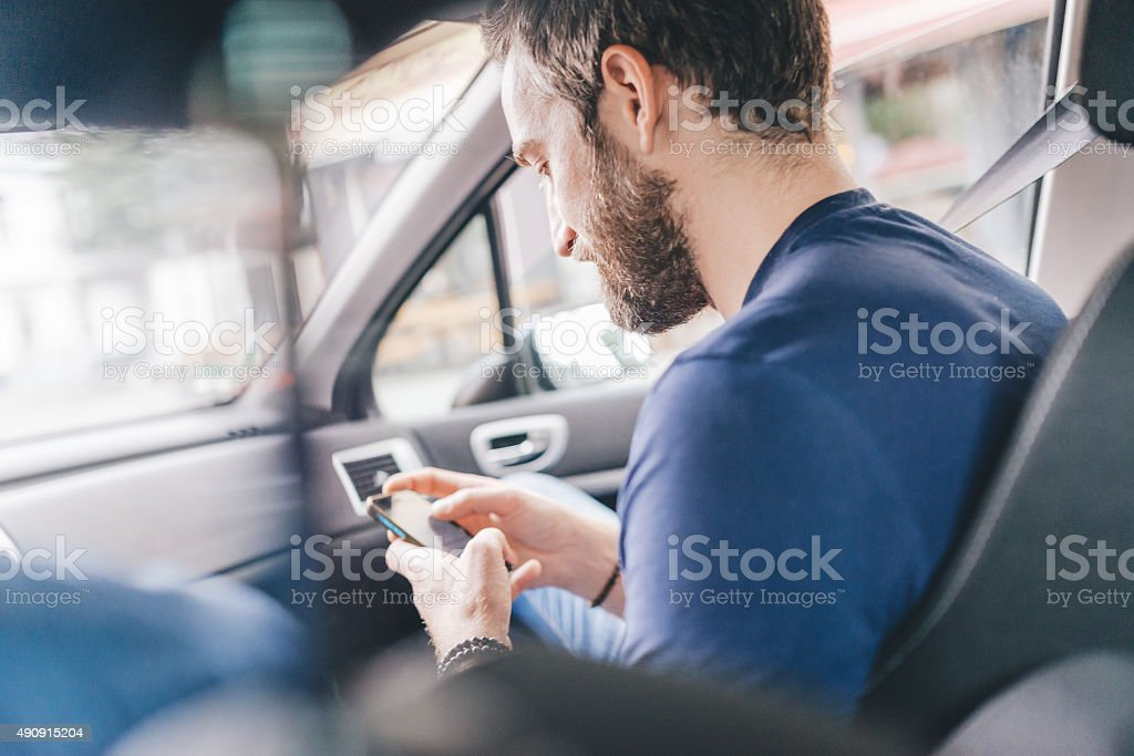 man using smartphone and sending message seating in a car stock photo