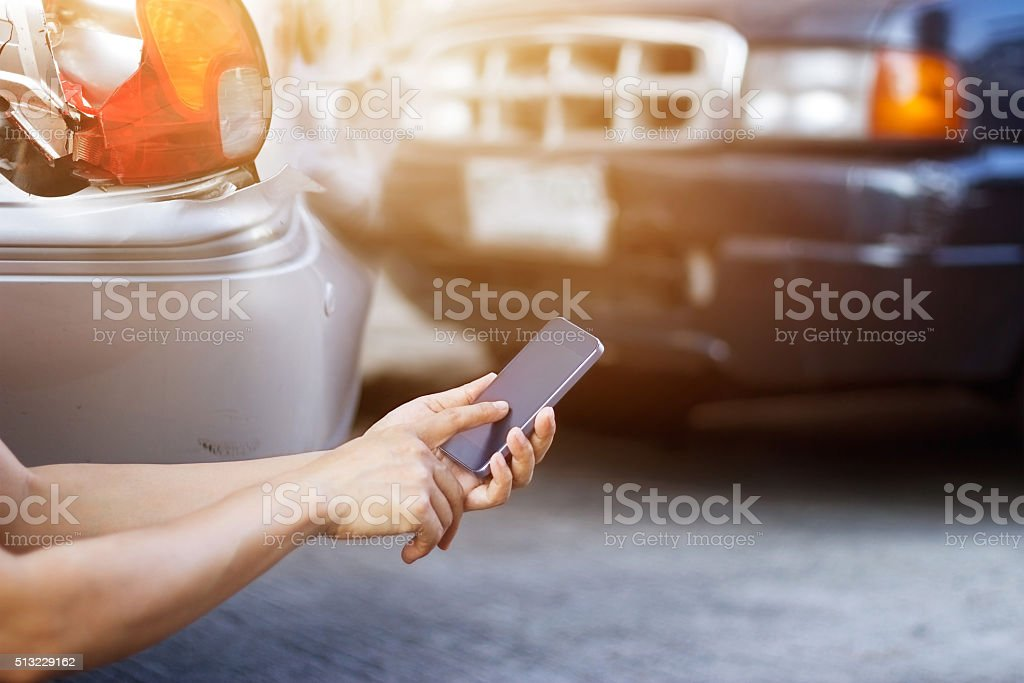 Man using smartphone at roadside after traffic accident stock photo