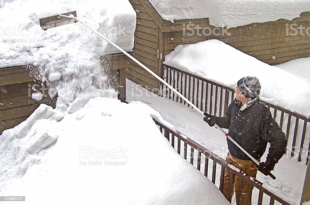 man using snow rake stock photo
