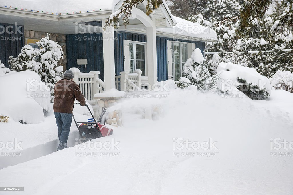 Man using snowblower in deep snow stock photo