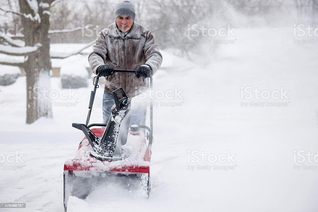 Man using snowblower in deep snow stock photo