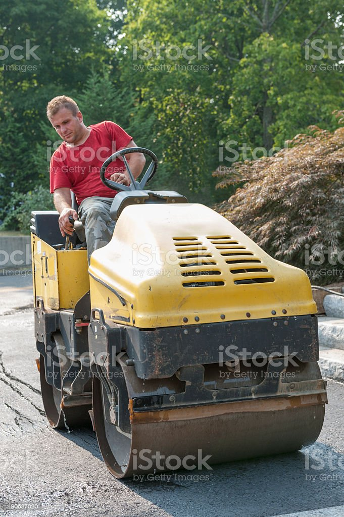A man is using a heavy steam roller, a tool which professionals use...
