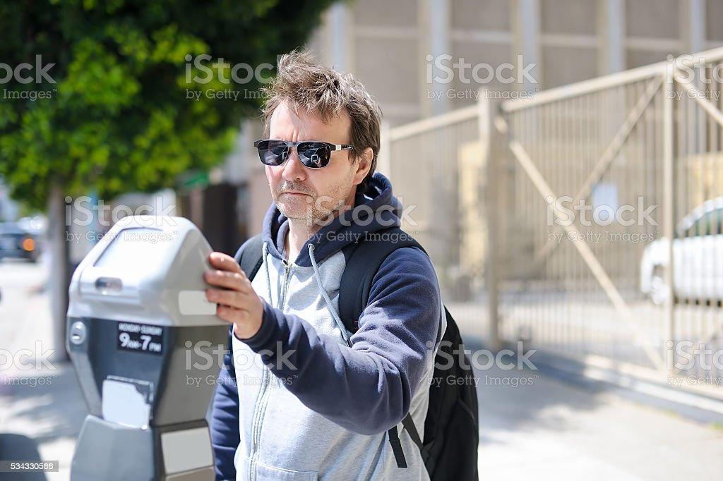 Man using street parking meter stock photo