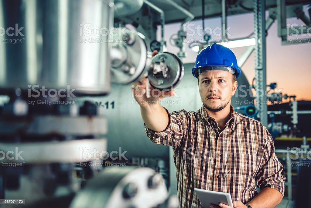 Man using tablet at Natural gas processing facility stock photo