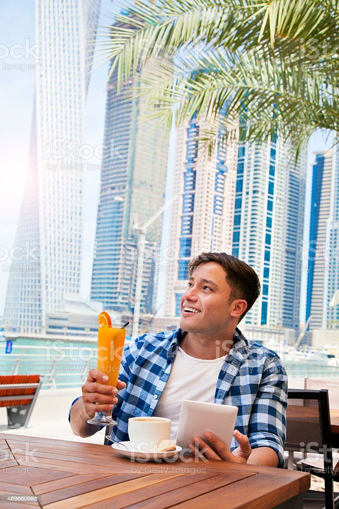 Man using tablet computer in cafe in Dubai Marina stock photo