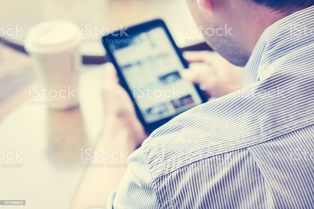 Man using tablet pc in coffee shop stock photo