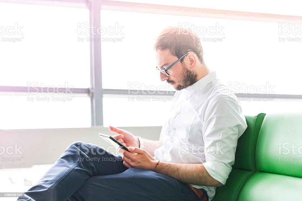 man using tablet waiting at the gate in a airport stock photo
