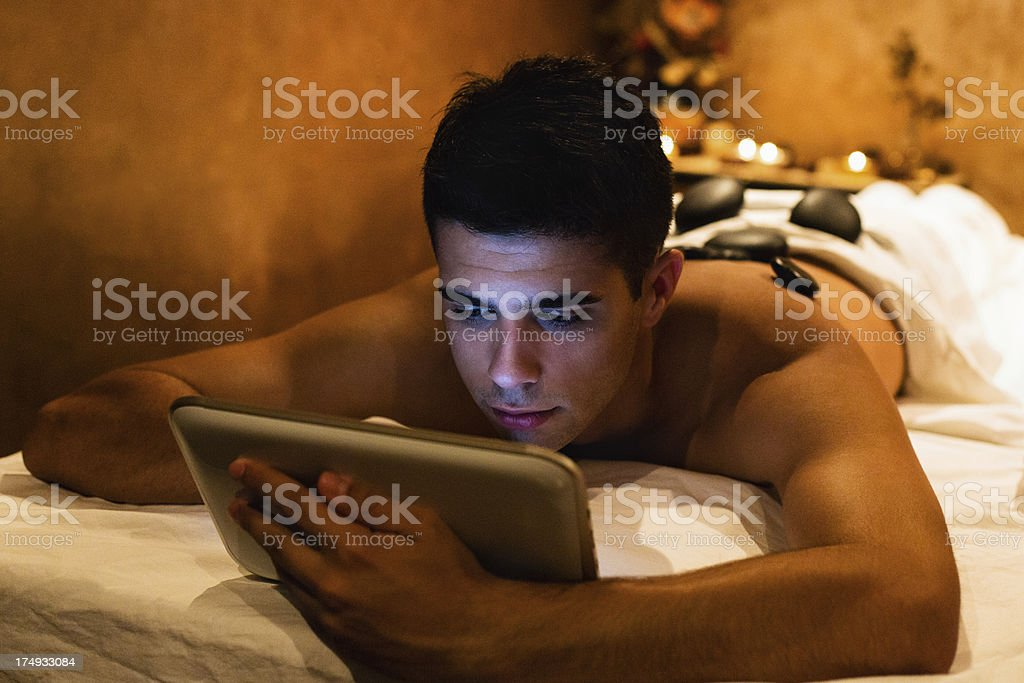 Man using tablet while having a massage royalty-free stock photo