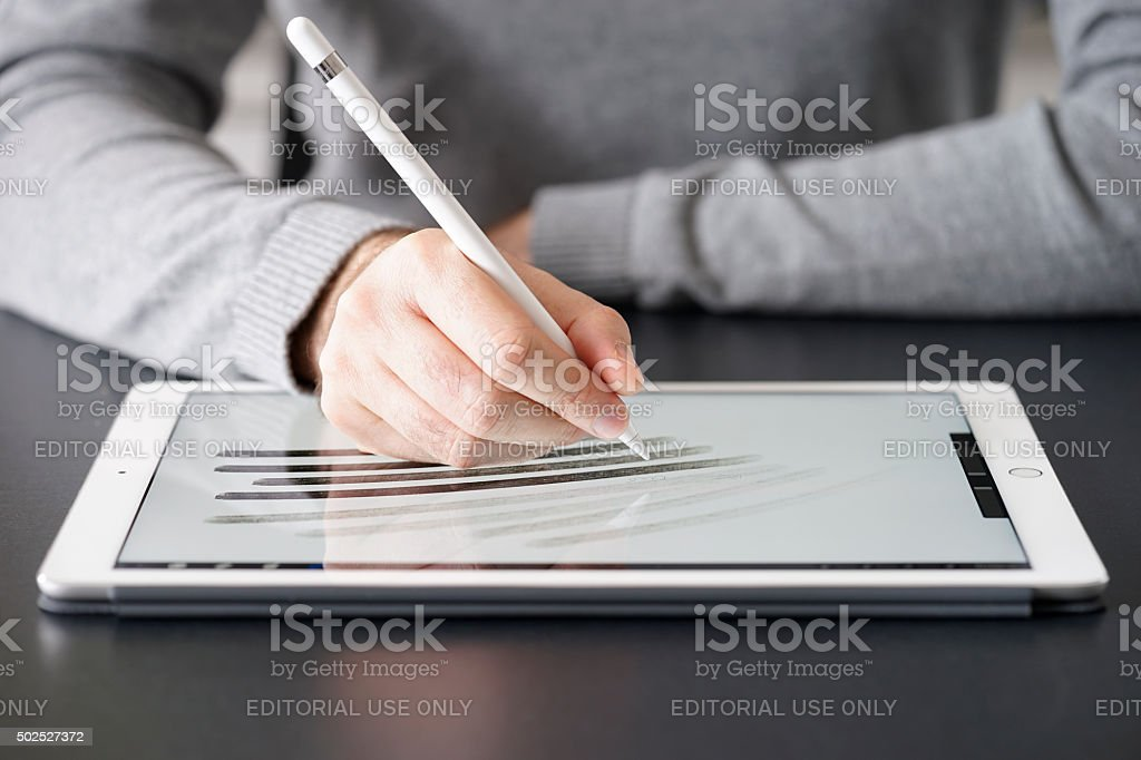 Man using the Apple Pencil on a white iPad Pro stock photo