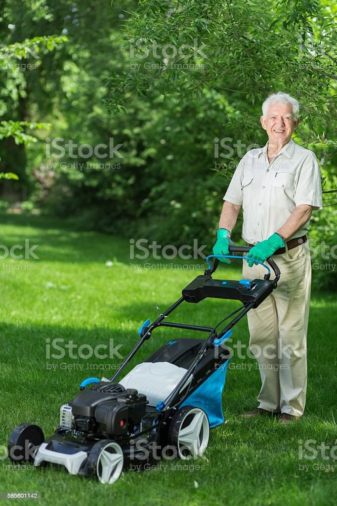 Man using the lawnmower stock photo