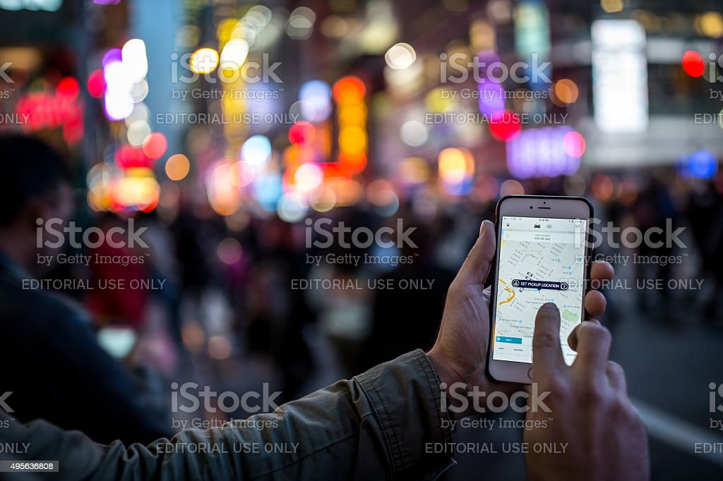 Man Using the Uber Taxi App on Iphone in NYC stock photo