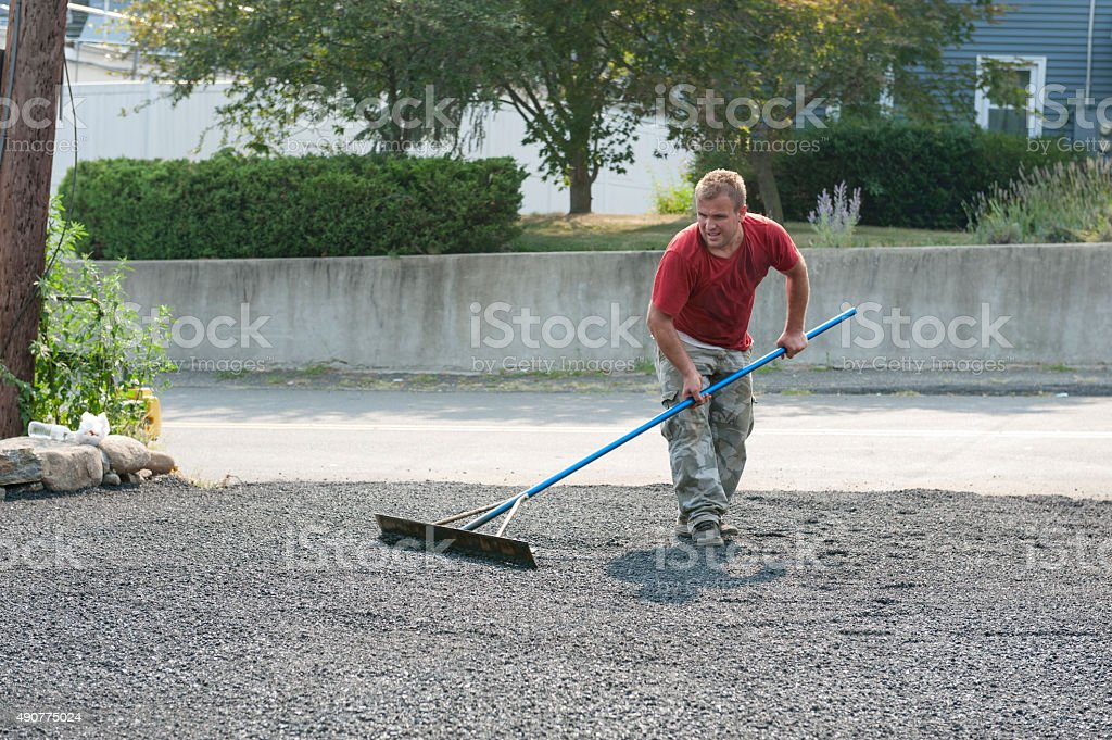 Man using tool to smooth asphalt on new driveway stock photo
