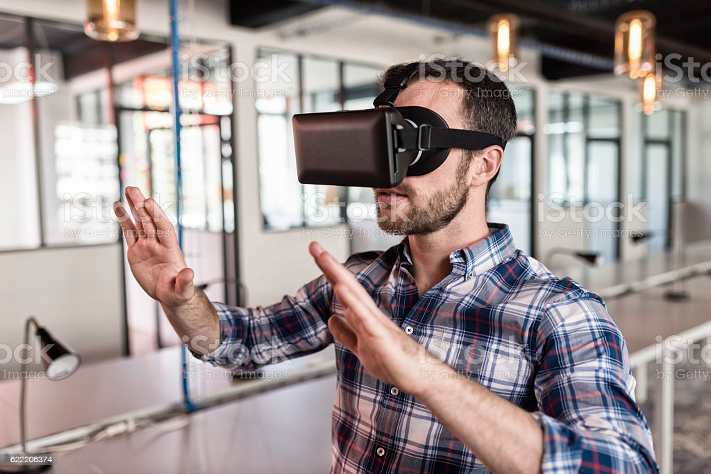 Man using virtual reality glasses in startup office. stock photo