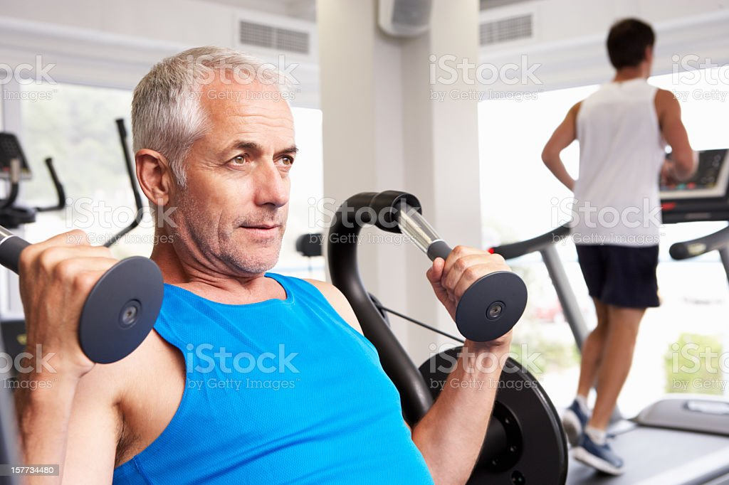 Man Using Weights Machine With Runner On Treadmill In Background royalty-free stock photo
