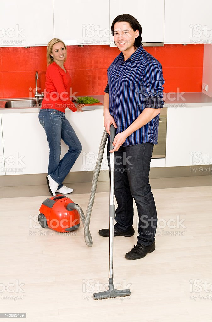 Man vacuuming, woman in background royalty-free stock photo