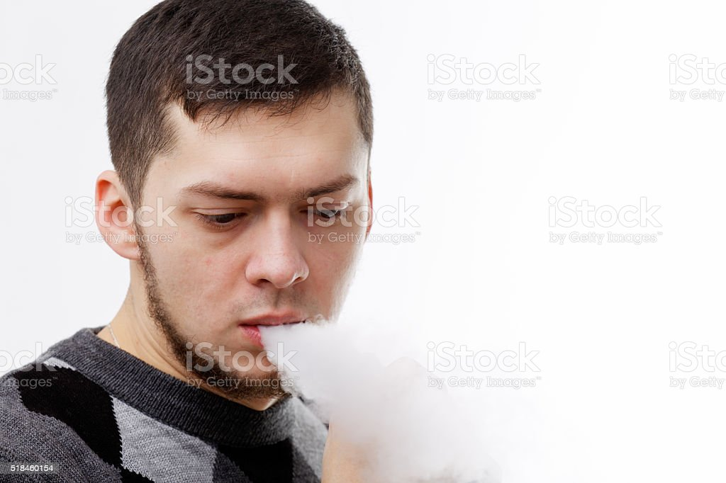 Man vaping (smoking an electronic cigarette) on a white background stock photo