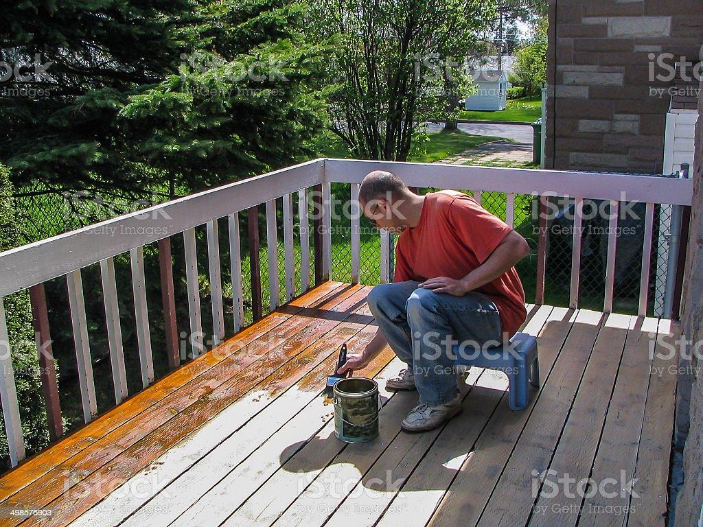 Man varnishing his deck stock photo