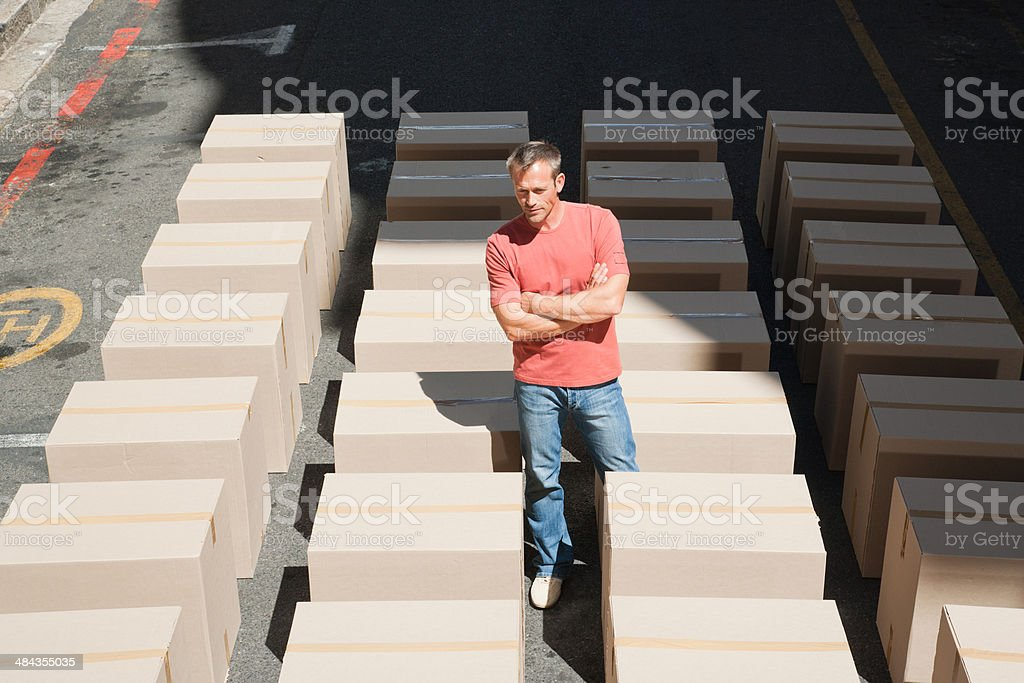 Man viewing lines of boxes in roadway stock photo