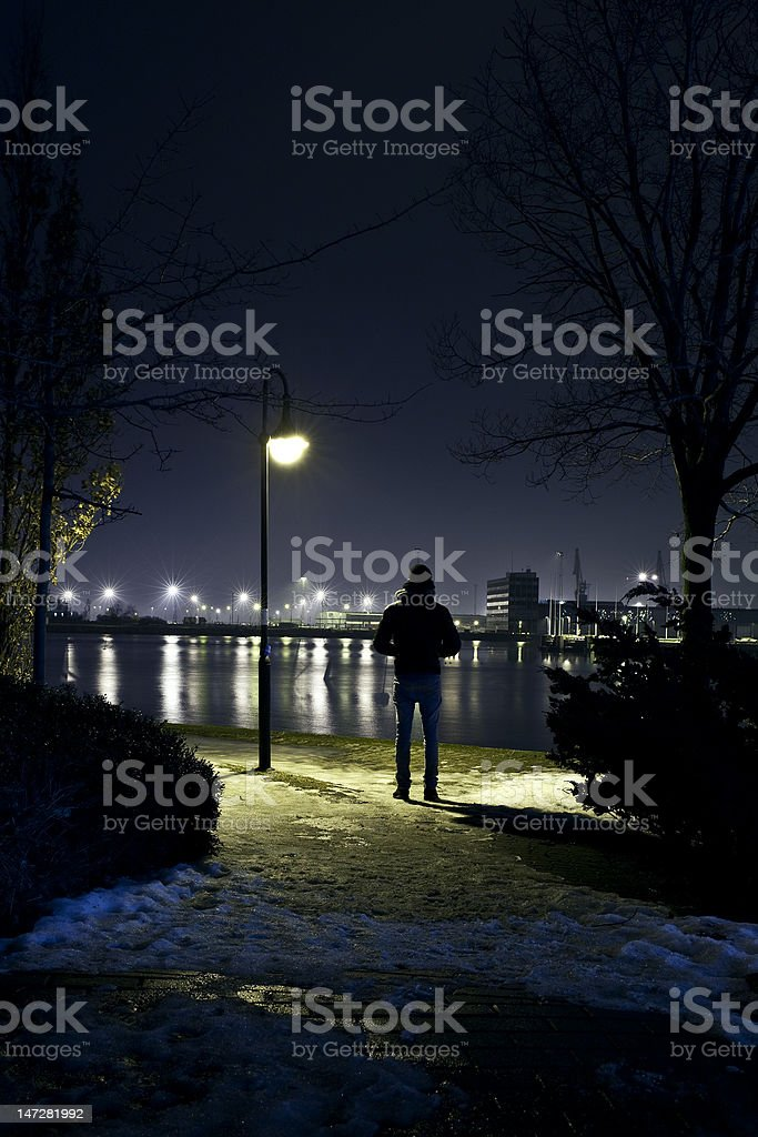 man viewing the sea under a street lamp royalty-free stock photo