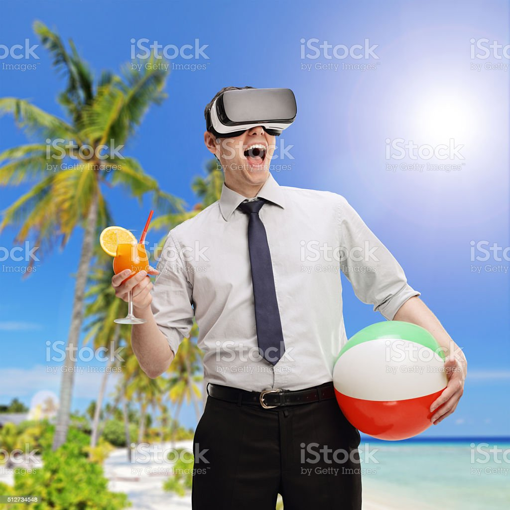 Man visualizing a beach using a VR headset stock photo