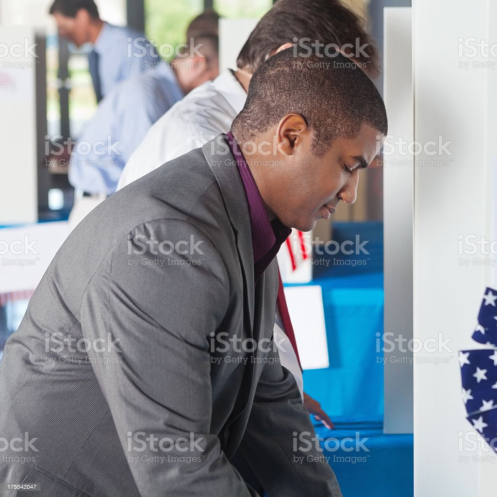 Man voting at a busy vote location royalty-free stock photo
