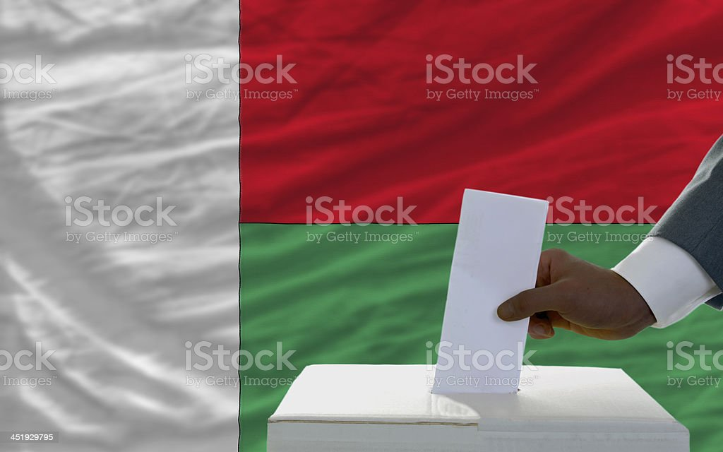 man voting on elections in front flag of madagascar royalty-free stock photo