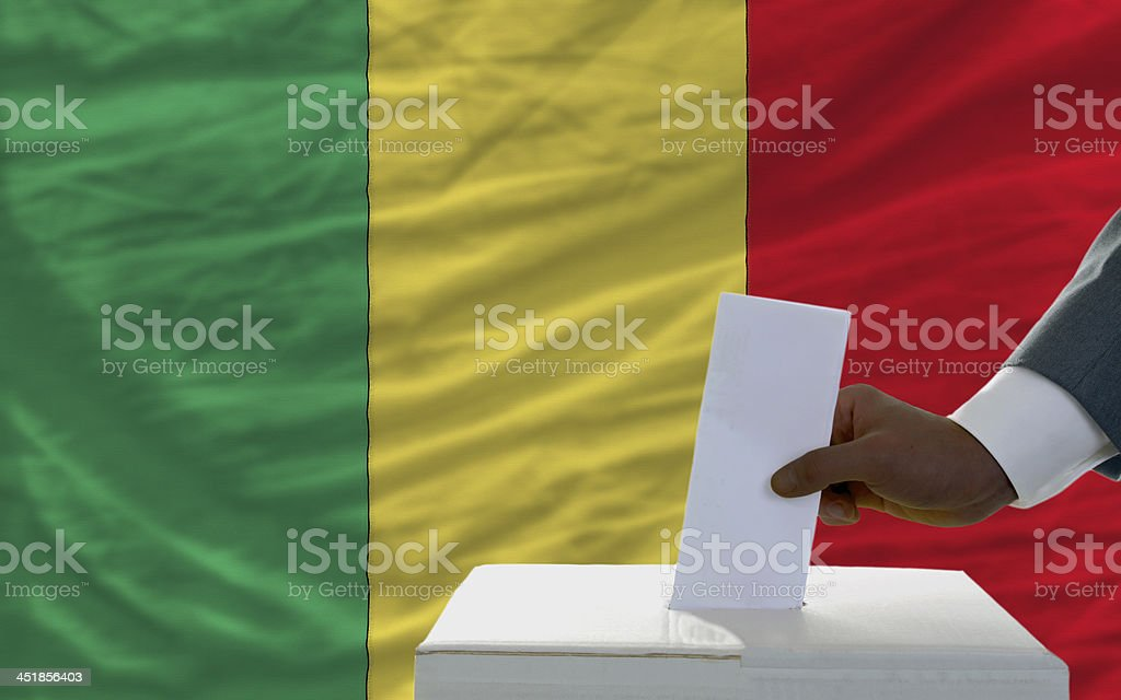 man voting on elections in front flag of mali royalty-free stock photo