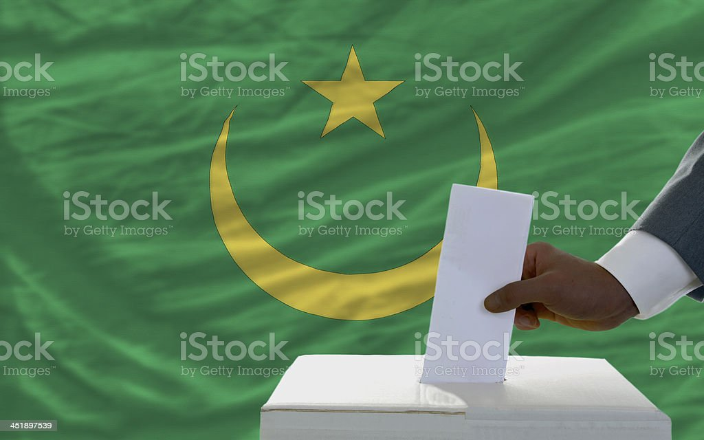 man voting on elections in front flag of mauritania stock photo