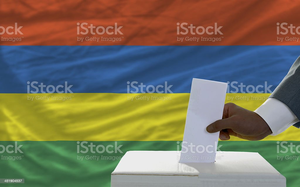 man voting on elections in front flag of mauritius stock photo