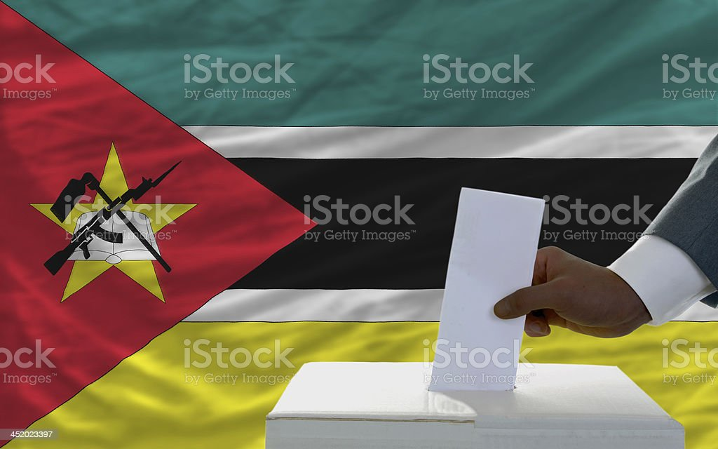 man voting on elections in front flag of mozambique royalty-free stock photo
