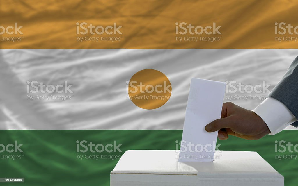 man voting on elections in front flag of niger royalty-free stock photo