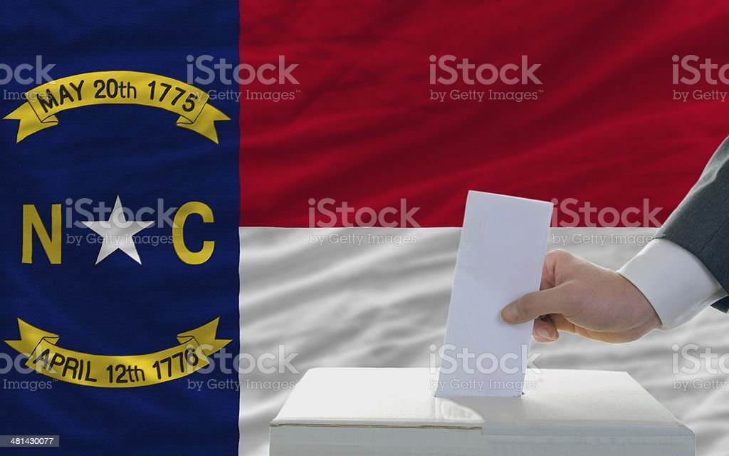 man voting on elections in front  flag of north carolina royalty-free stock photo