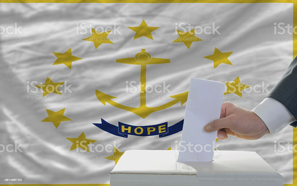 man voting on elections in front  flag of rhode island royalty-free stock photo