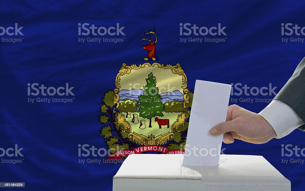 man voting on elections in front flag of vermont royalty-free stock photo